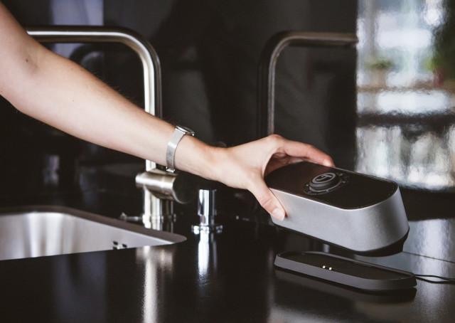 Un bras qui pose une enceinte nomade sur la planche de travail dans la cuisine