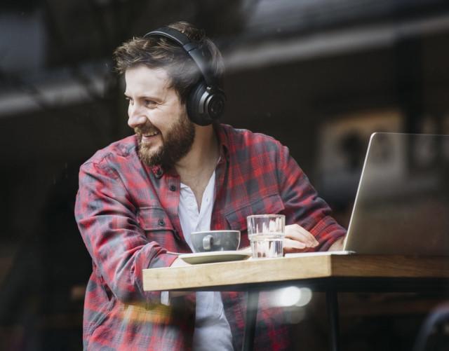 Homme avec casque audio Bluetooth au café