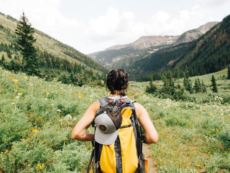 Rückenansicht einer Frau vor Bergkulisse